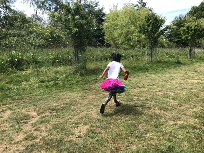 A young black mixed girl running in a field carefree in a pink tutu