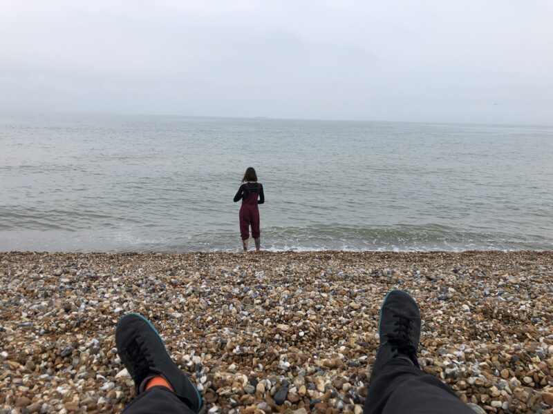 a person lying on a beach looking out to sea with another person in the distance
