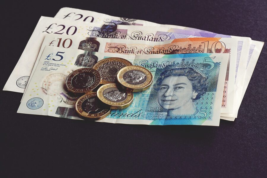 photo of five pound note and some coins.