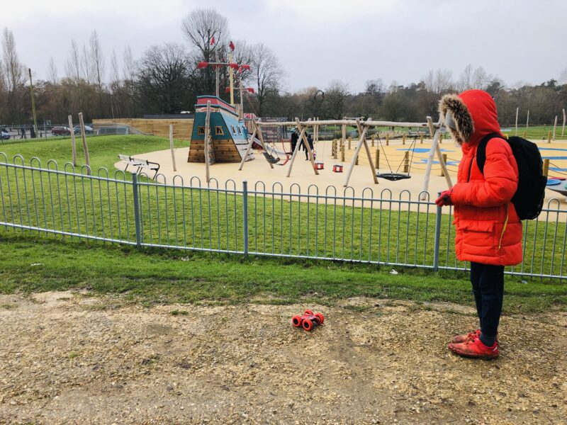 Boy playing with remote control car in a park