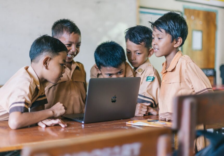 young boys in a classroom around a laptop
